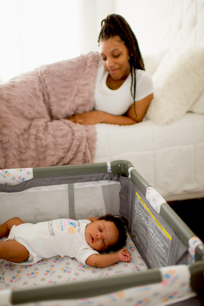 Mother in bed looking at baby sleeping in a safe sleep environment